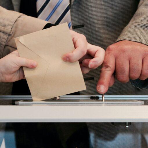 Wahlumschlag wird in Wahlurne eingegeben, Wahlhelfer kontorlliert